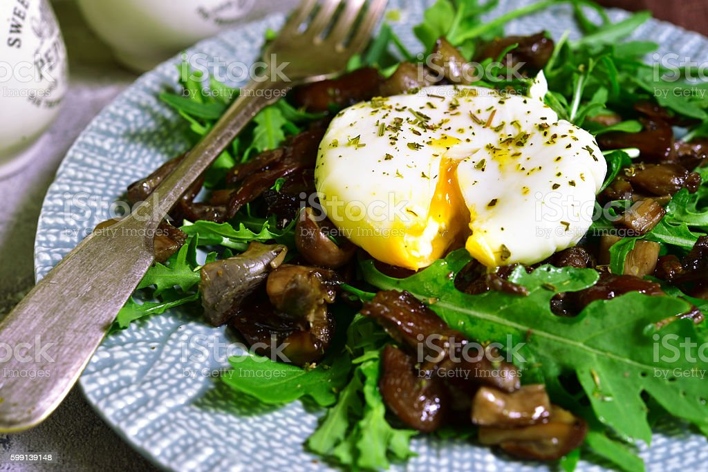 Warm mushroom salad with arugula and poached egg. stock photo
