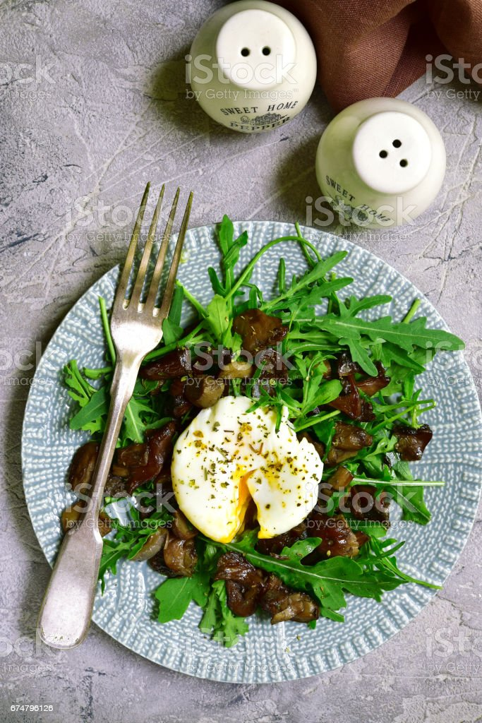 Warm mushroom salad with arugula and poached egg stock photo