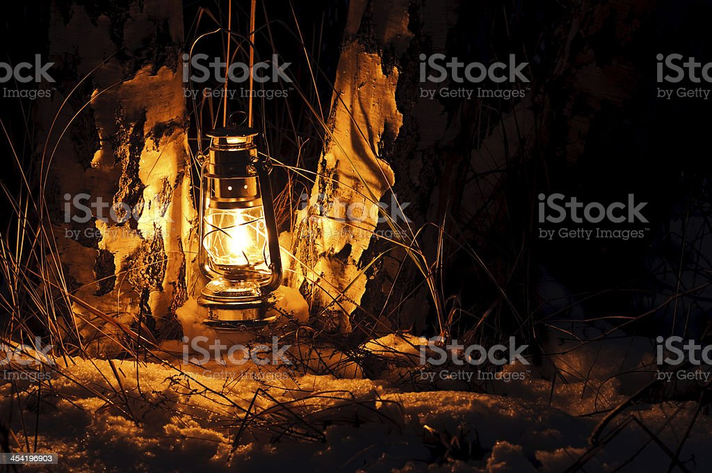 Warm oil lamps light in the snow stock photo