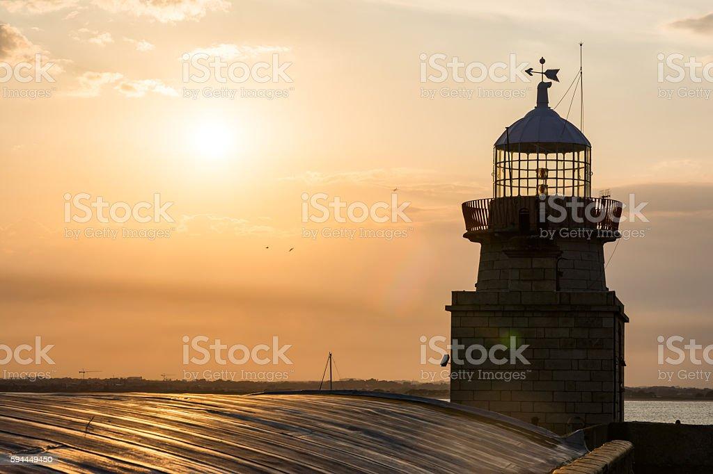 Warm Orange Sunset Sky over Howth Lighthouse Tower Ireland stock photo
