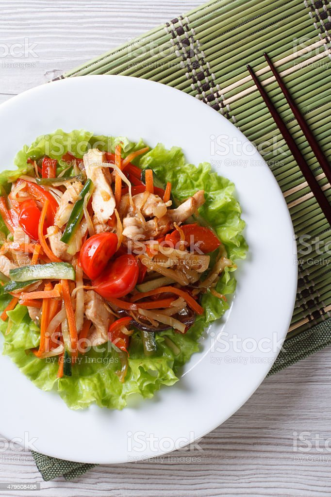 warm salad with chicken and vegetables. Vertical top view stock photo