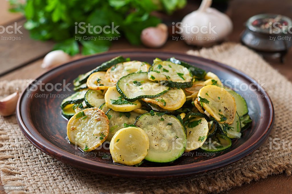 Warm salad with young zucchini with garlic and herbs stock photo