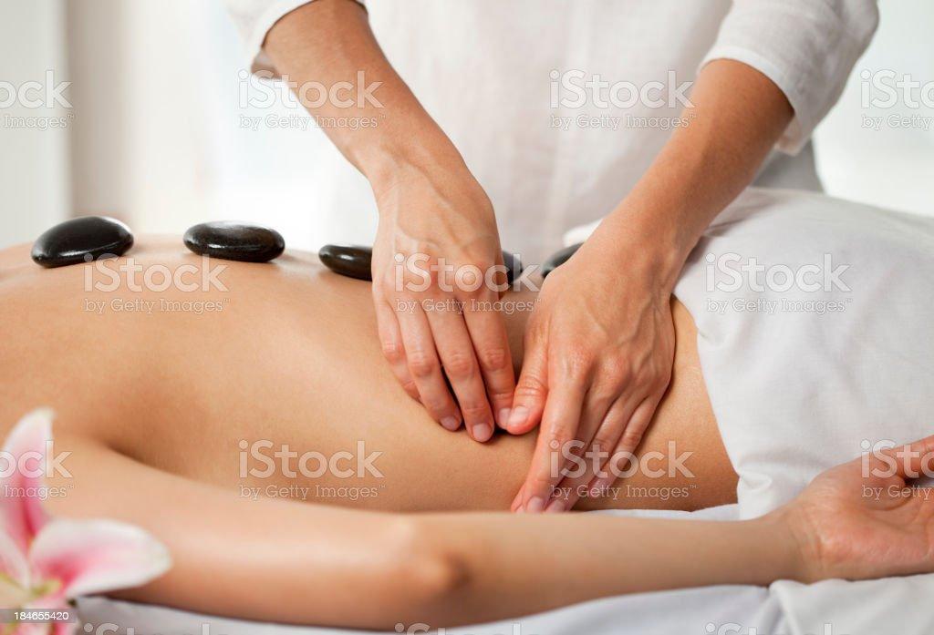 Warm stone massage at spa stock photo