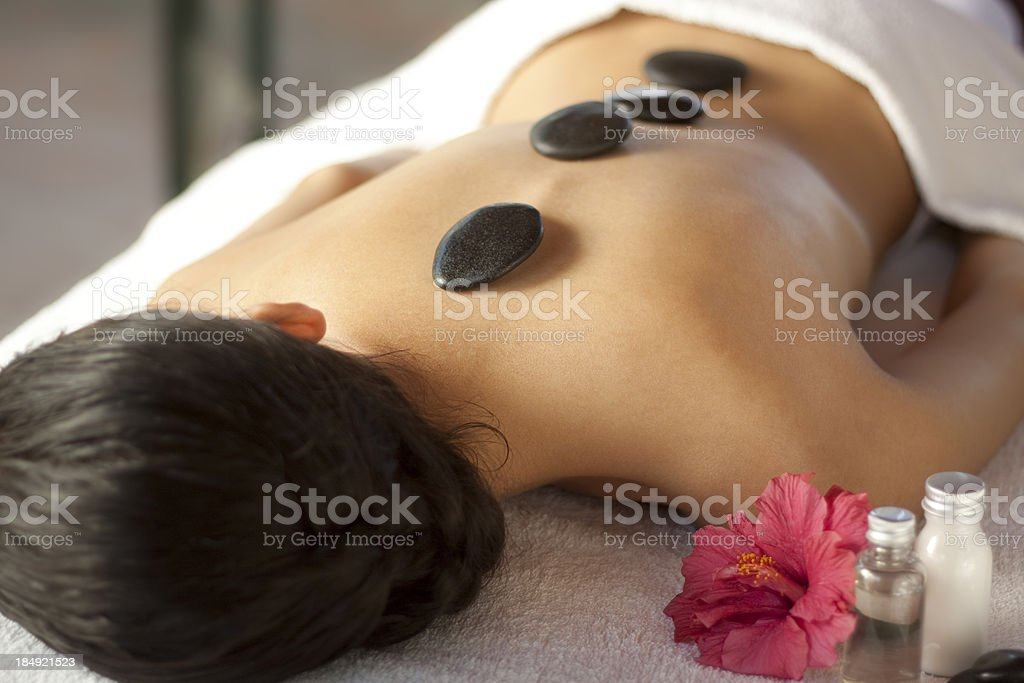 Warm stone massage at spa stock photo