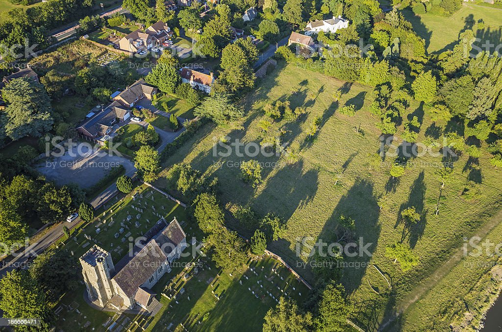Warm sunlight on tranquil country village and church aerial photograph royalty-free stock photo