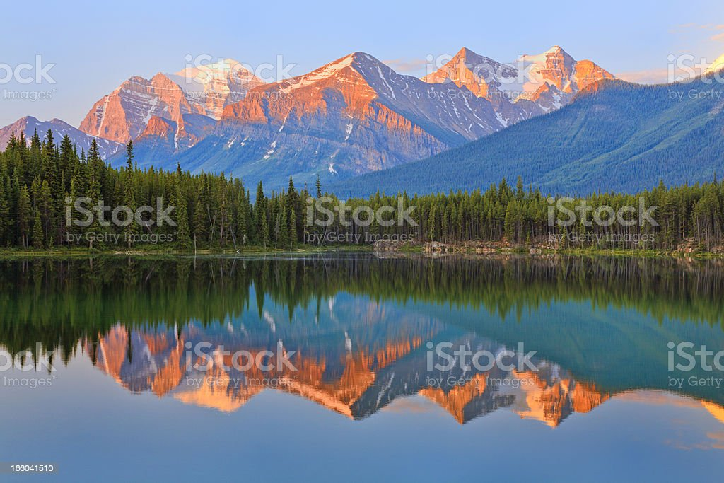 warm sunrise colors, Canadian Rocky Mountains, mirror reflection, blue lake royalty-free stock photo