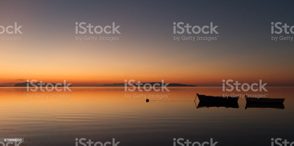 A warm sunset on a calm water stock photo