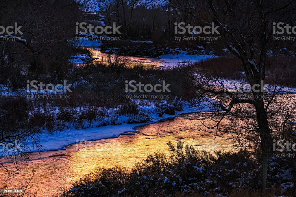 Warm Sunset Reflections on Eagle River in Winter stock photo