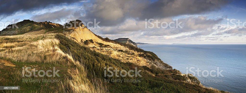 Warm sunshine rakes across the Dorset Jurassic Coast at sunset stock photo