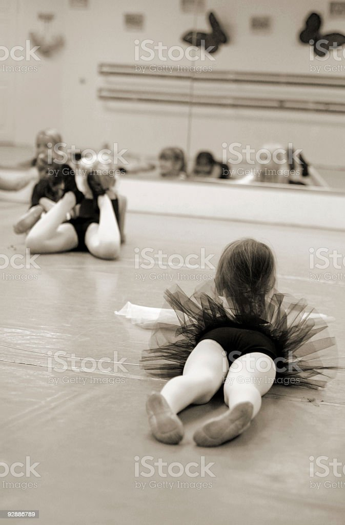 Warm up and stretching in the ballet class (sepia) stock photo