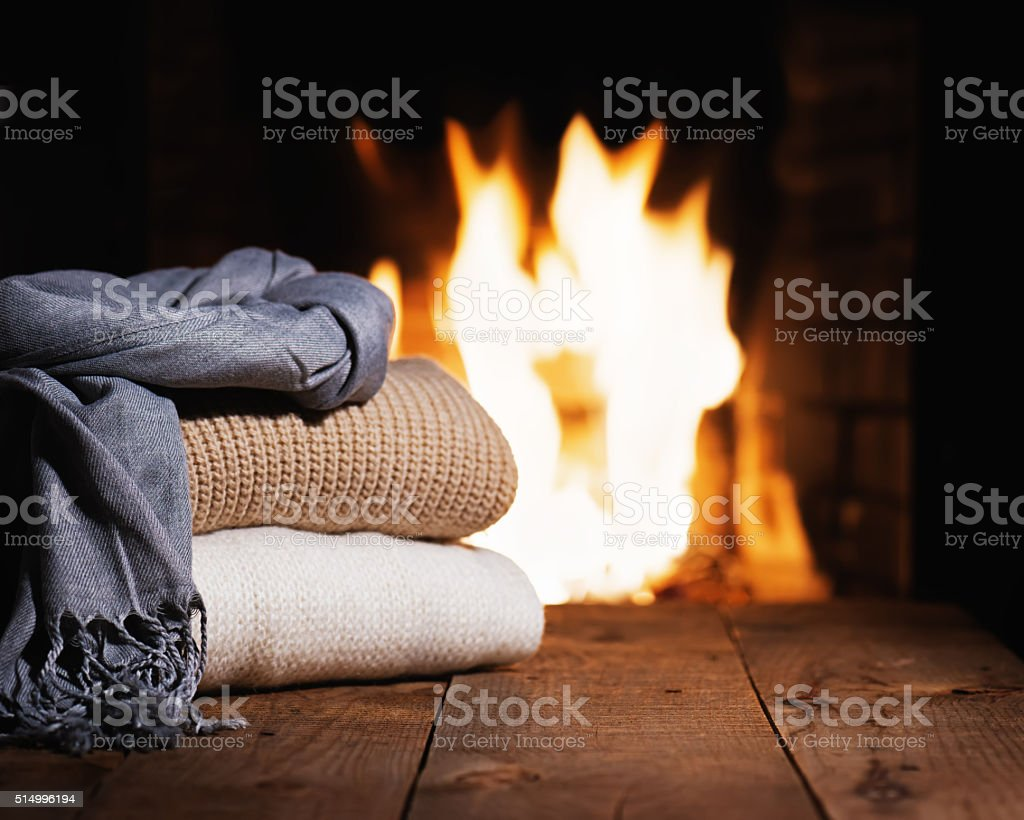 Warm woolen things near fireplace on wooden table. stock photo