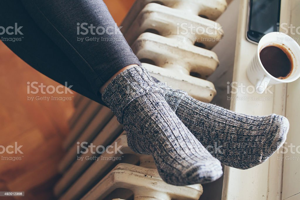 warming by the radiator stock photo