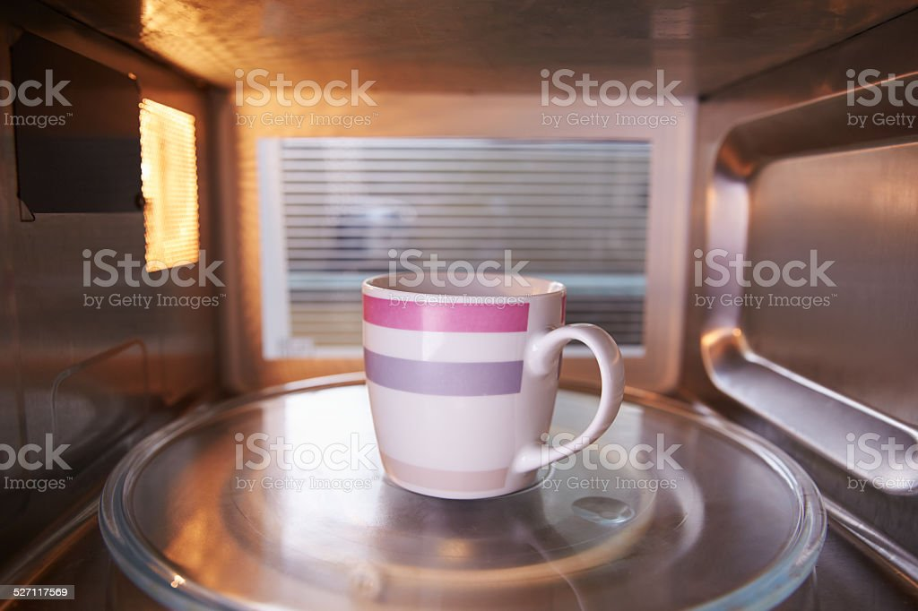 Warming Cup Of Coffee Inside Microwave Oven stock photo