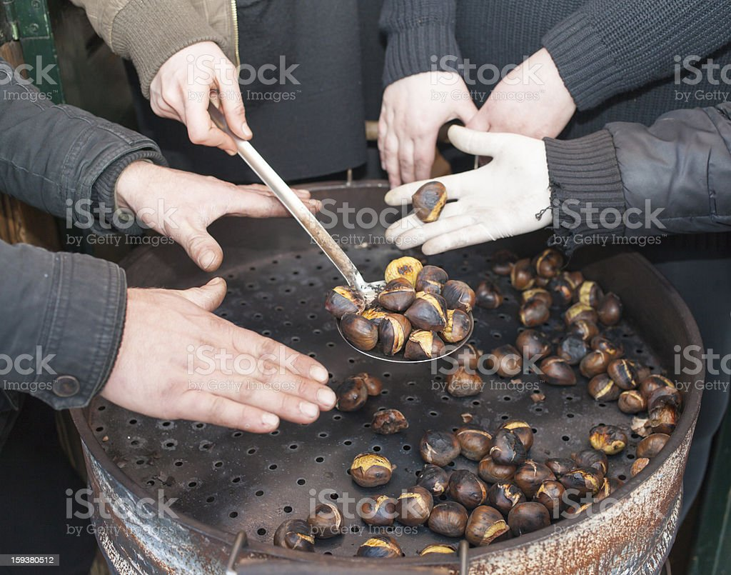 Warming hands on hot chestnuts royalty-free stock photo