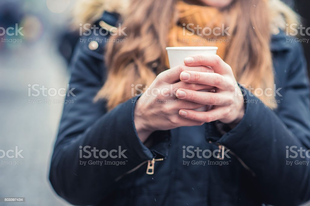 Warming her hands with coffee stock photo