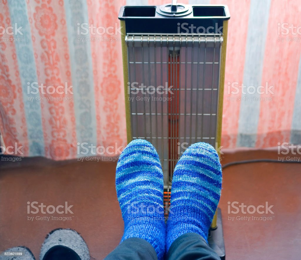 Warming of feet a heater with a quartz lamp. stock photo