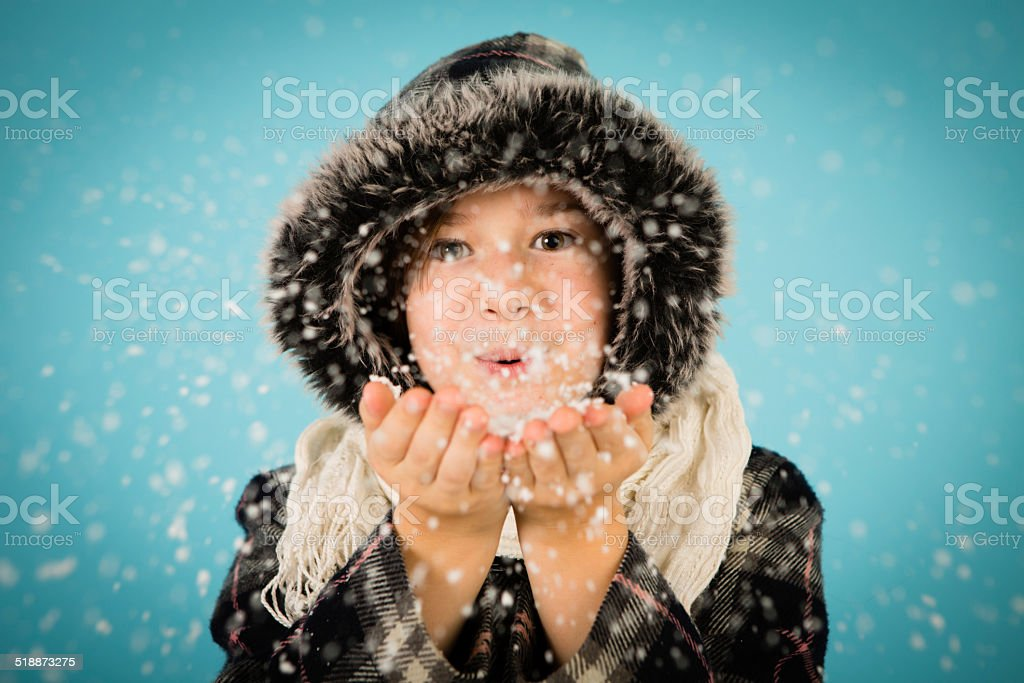 Warmly Dressed Little Girl Blowing Handful of Snow stock photo