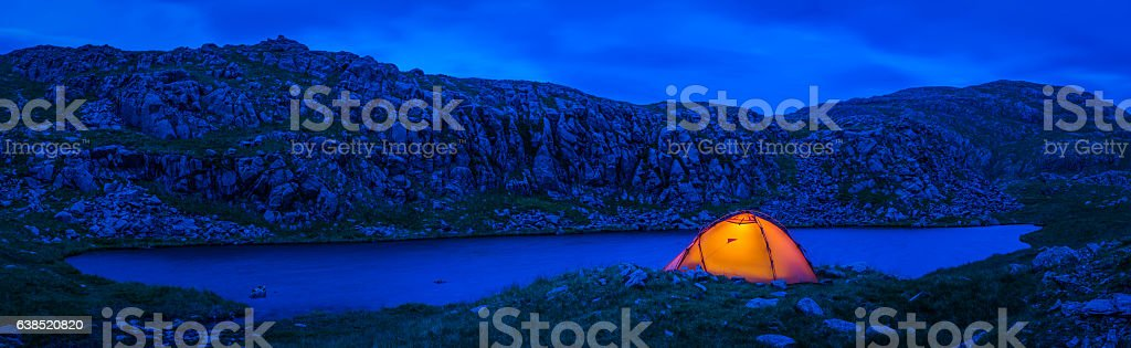 Warmly illuminated dome tent camping beside blue mountain lake panorama stock photo