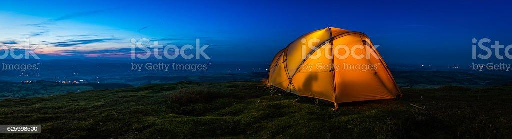 Warmly illuminated tent on mountain ridge overlooking sunset valley panorama stock photo