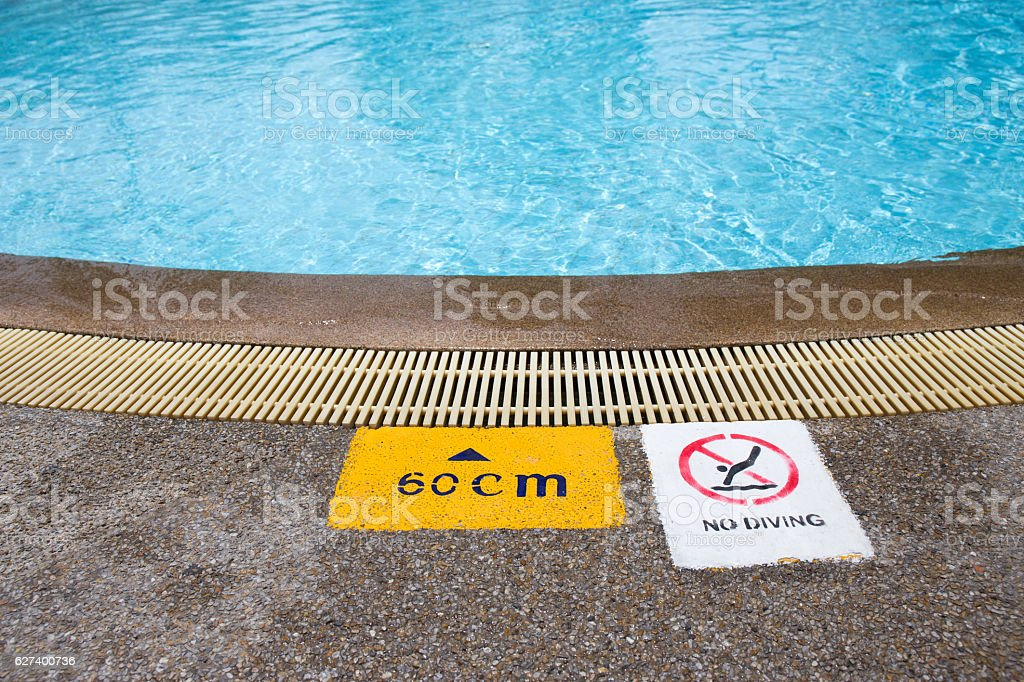 warning and depth sign at swimming pool for children stock photo