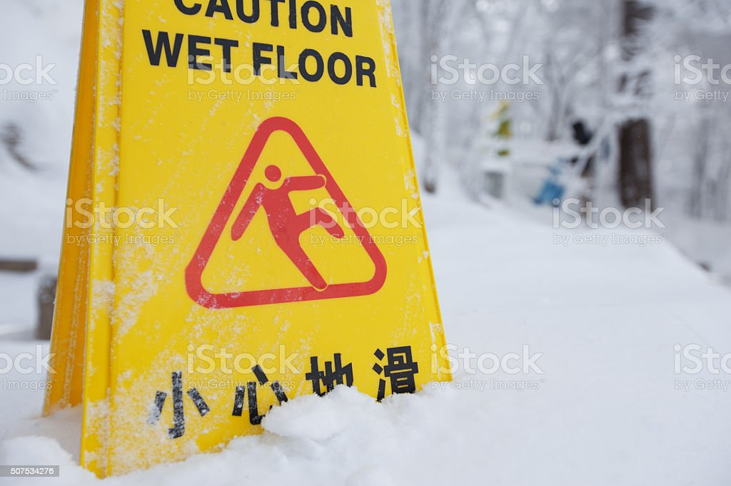 warning caution sign board on snow floor on hill stock photo