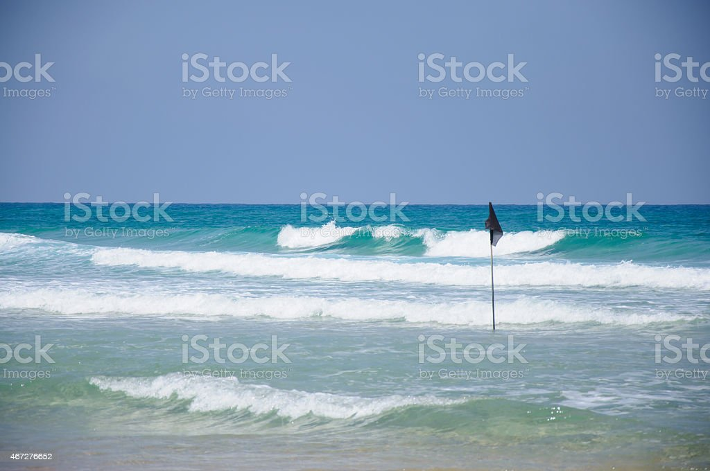 Warning flag in shallow water stock photo