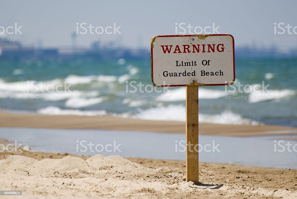 Warning Limit of Guarded Beach Signpost in the Sand stock photo