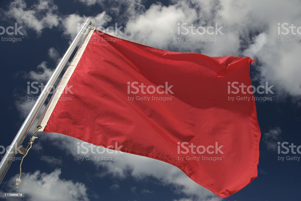 Warning Red Flag Waving in the Wind Blue Sky Clouds royalty-free stock photo