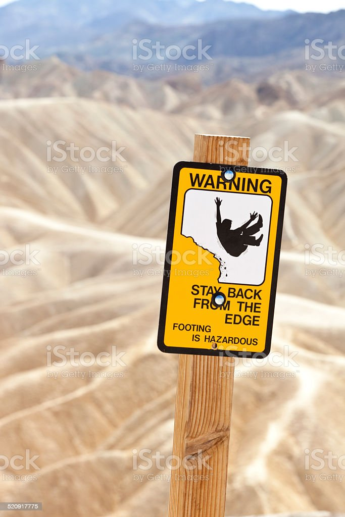 Warning sign along Zabriskie Point observation pathway Death Valley California stock photo