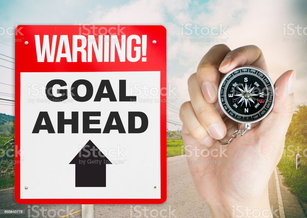 Warning sign goal ahead with hand holding compass for direction stock photo