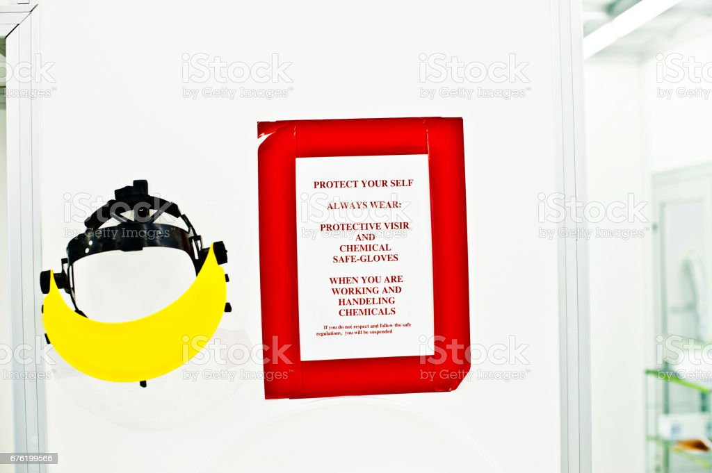 Warning Sign - Helmet (Visor) and Lab Instructions On Wall stock photo