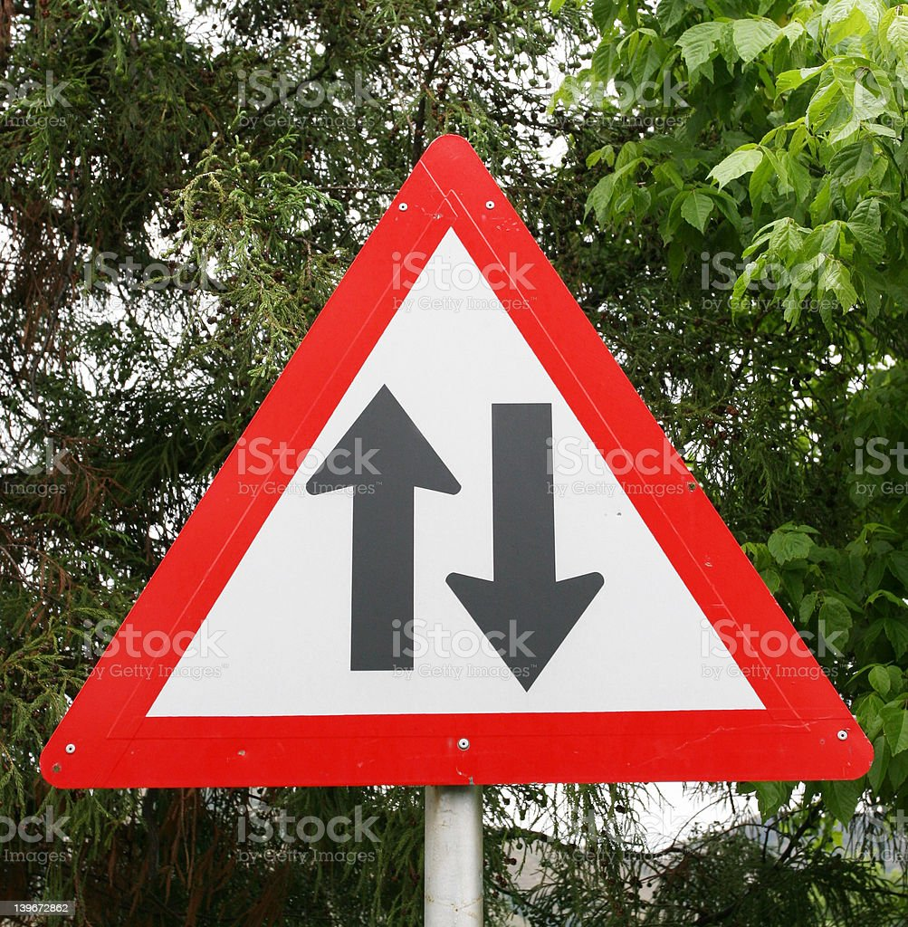 Warning sign of direction the traffic flows stock photo