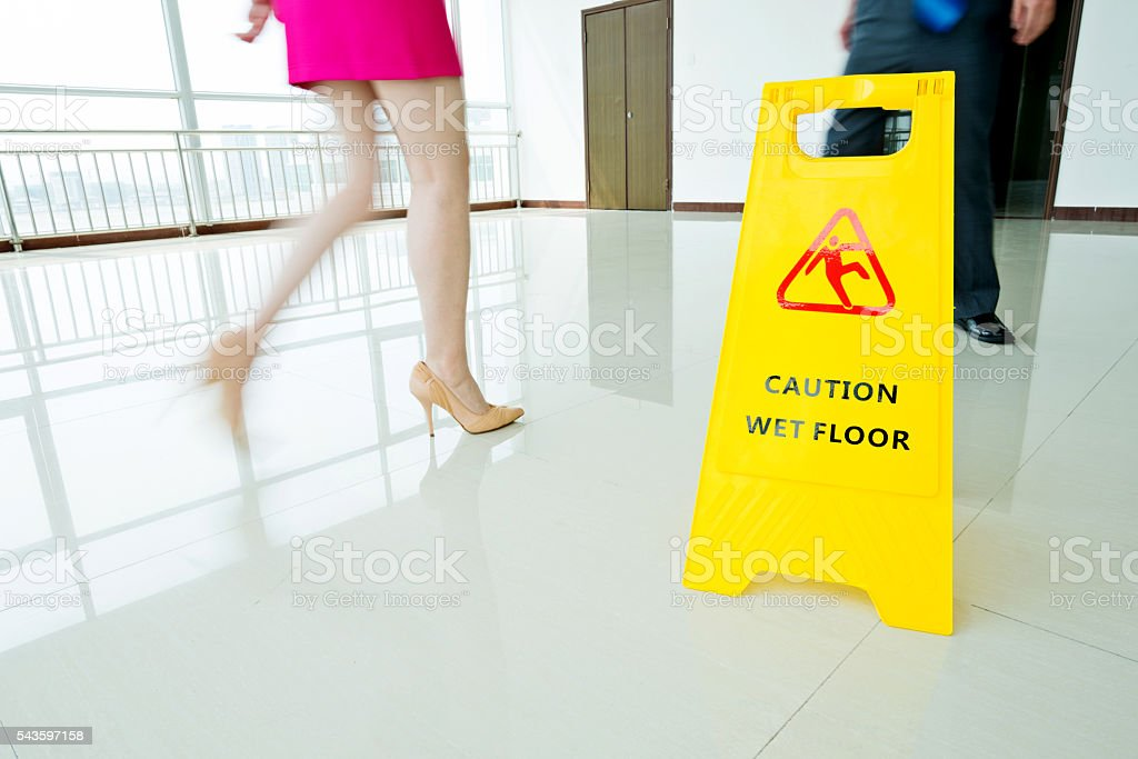 Warning sign slippery with motion blurred legs walking stock photo