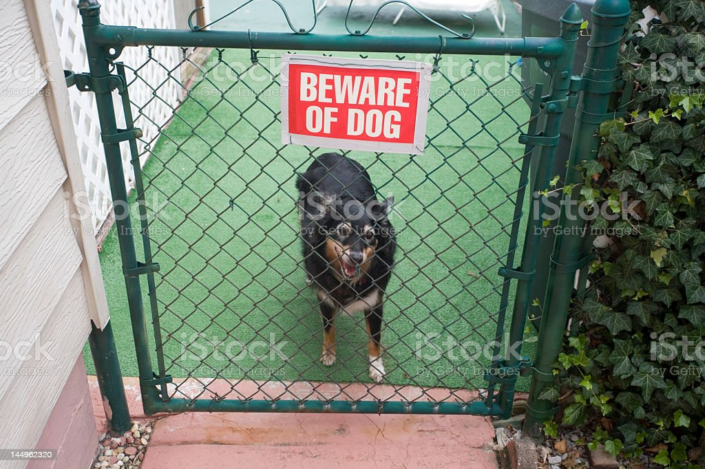 A warning sign with a dog standing behind a gate stock photo