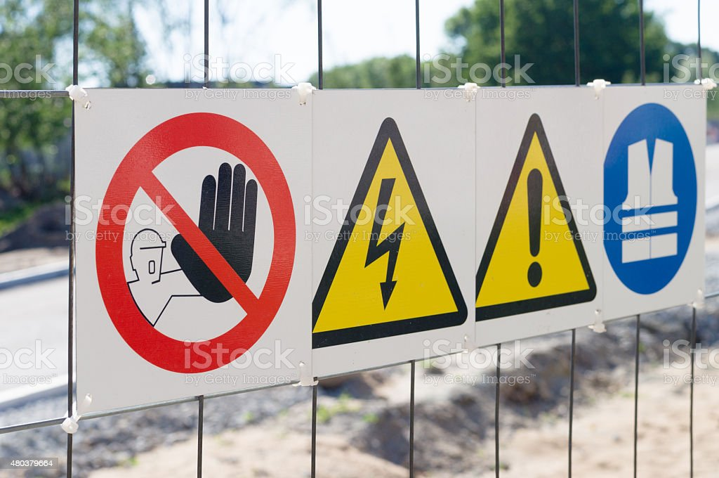 Warning signs on fence at construction site stock photo