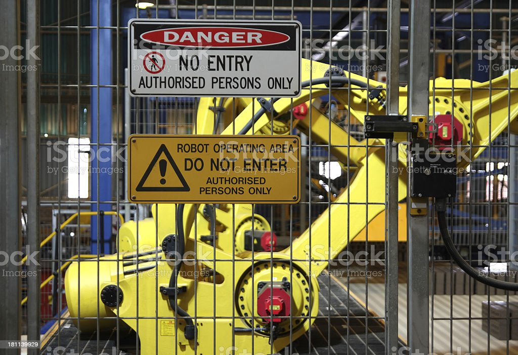 Warning signs outside robotic assembly line with robot in background stock photo