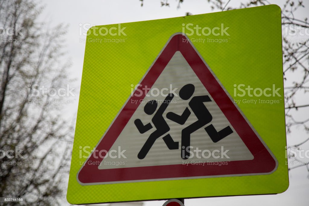 Warning yellow road sign school zone pedestrians closeup stock photo