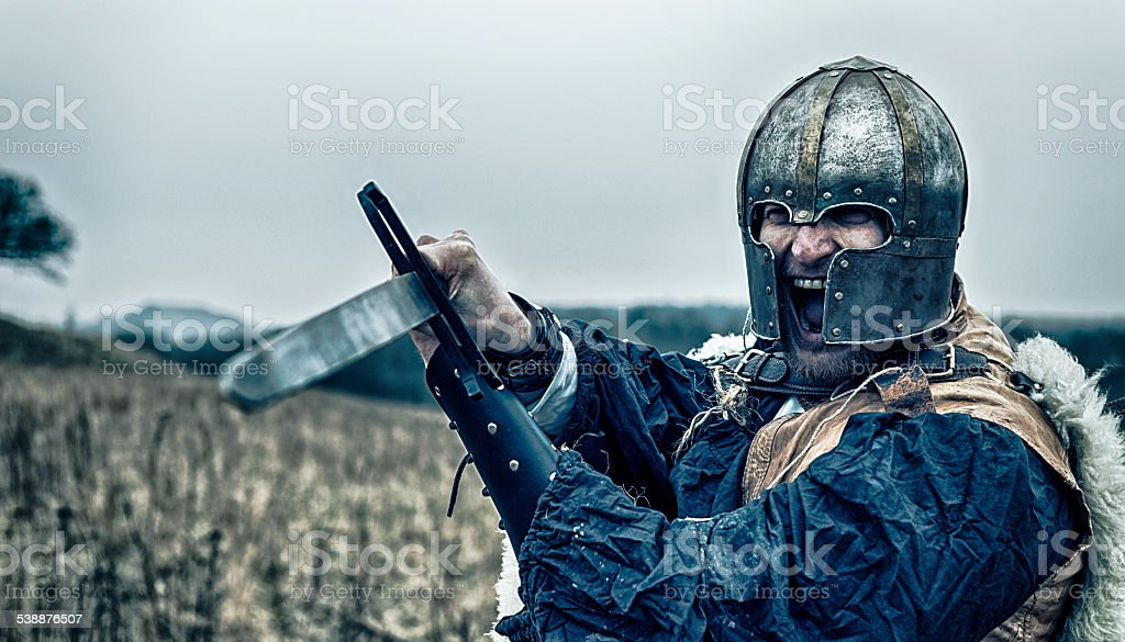Warrior attacks with a sword while screaming stock photo