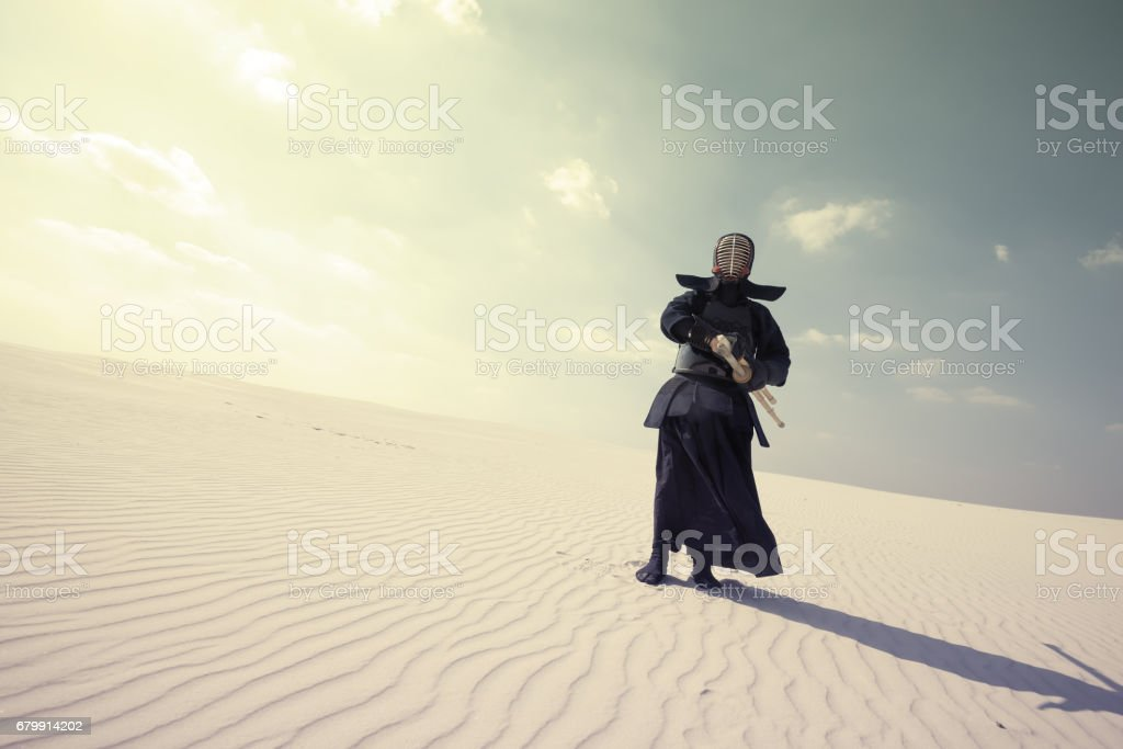 Warrior in traditional armor for kendo in a desert stock photo