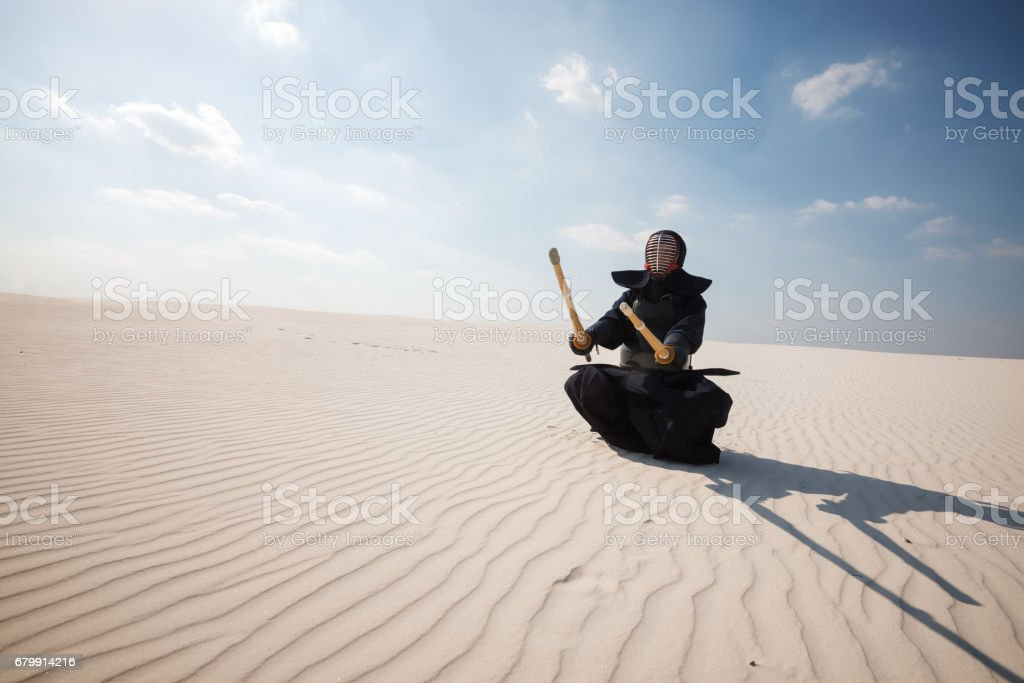 Warrior in traditional armor for kendo sits with swords in his hands stock photo