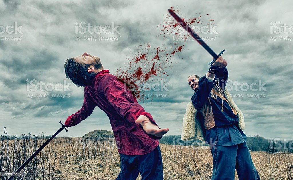 Warrior kills opponent with sword on a battlefield stock photo