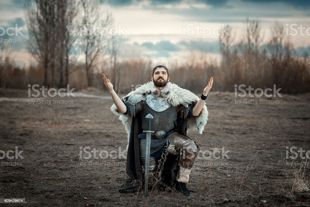 Warrior stood on one knee in the field. stock photo