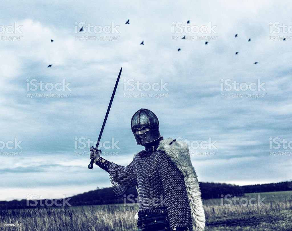 Warrior with helmet and sword ready to attack stock photo