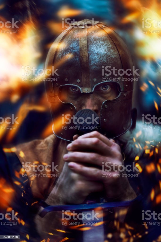 Warrior with helmet surrounded by flames stock photo