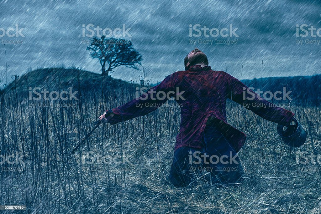 Warrior with sword and helmet falls to the ground stock photo