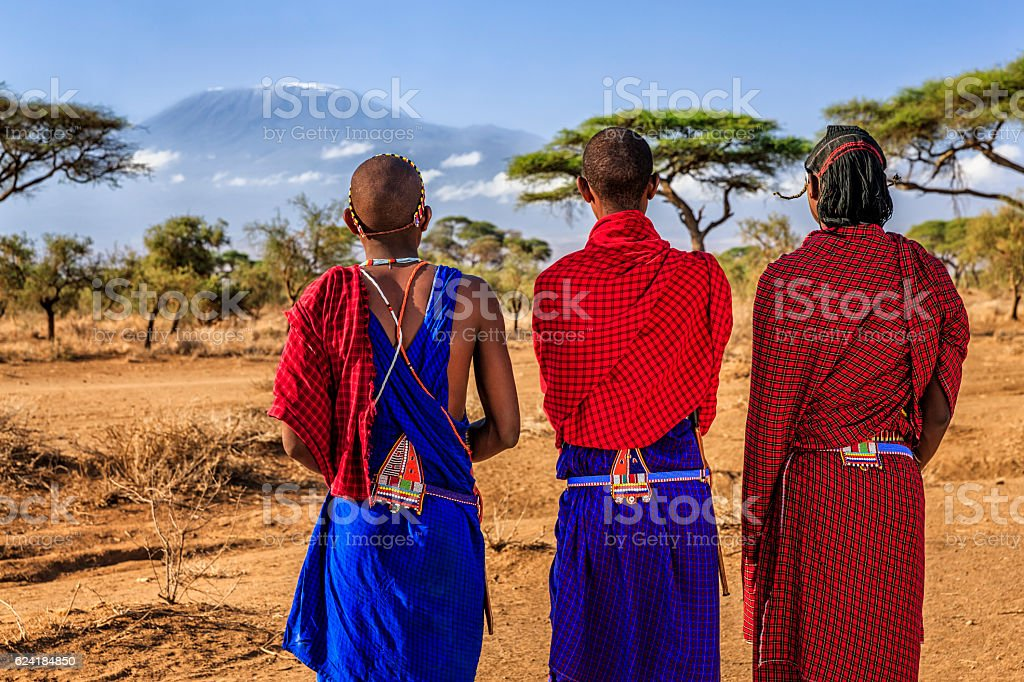 Warriors from Maasai tribe looking at Mount Kilimanjaro, Kenya, Africa stock photo