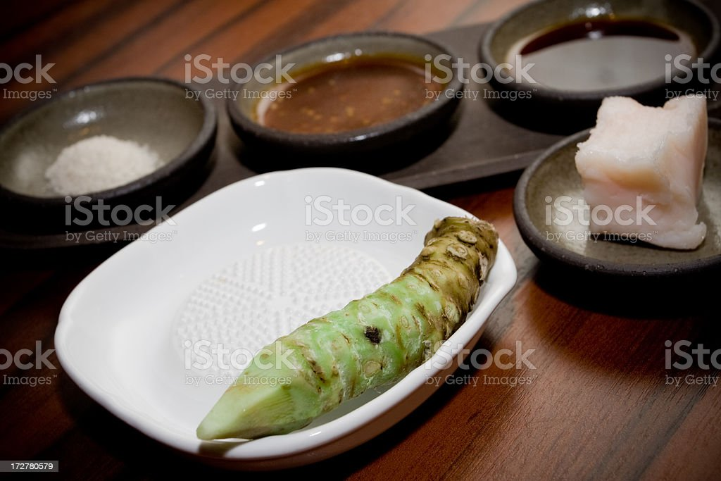 Wasabi root on a grater with dipping sauces stock photo