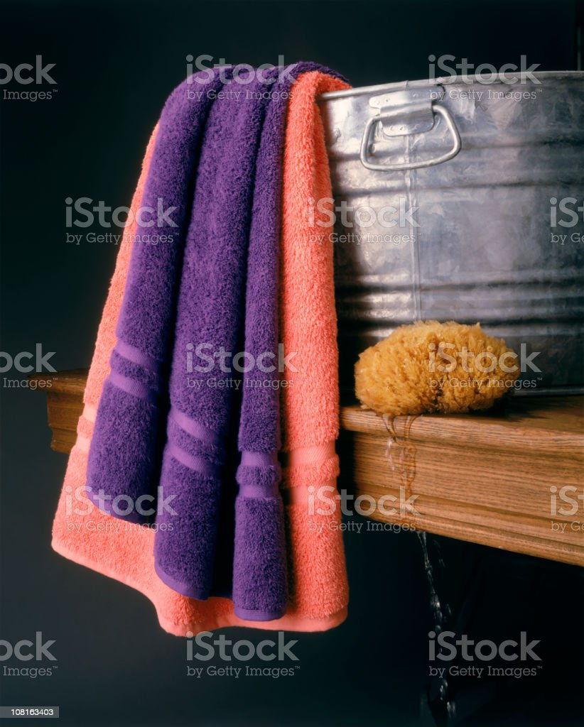 Wash Tub with Towels and Sponge on Table stock photo