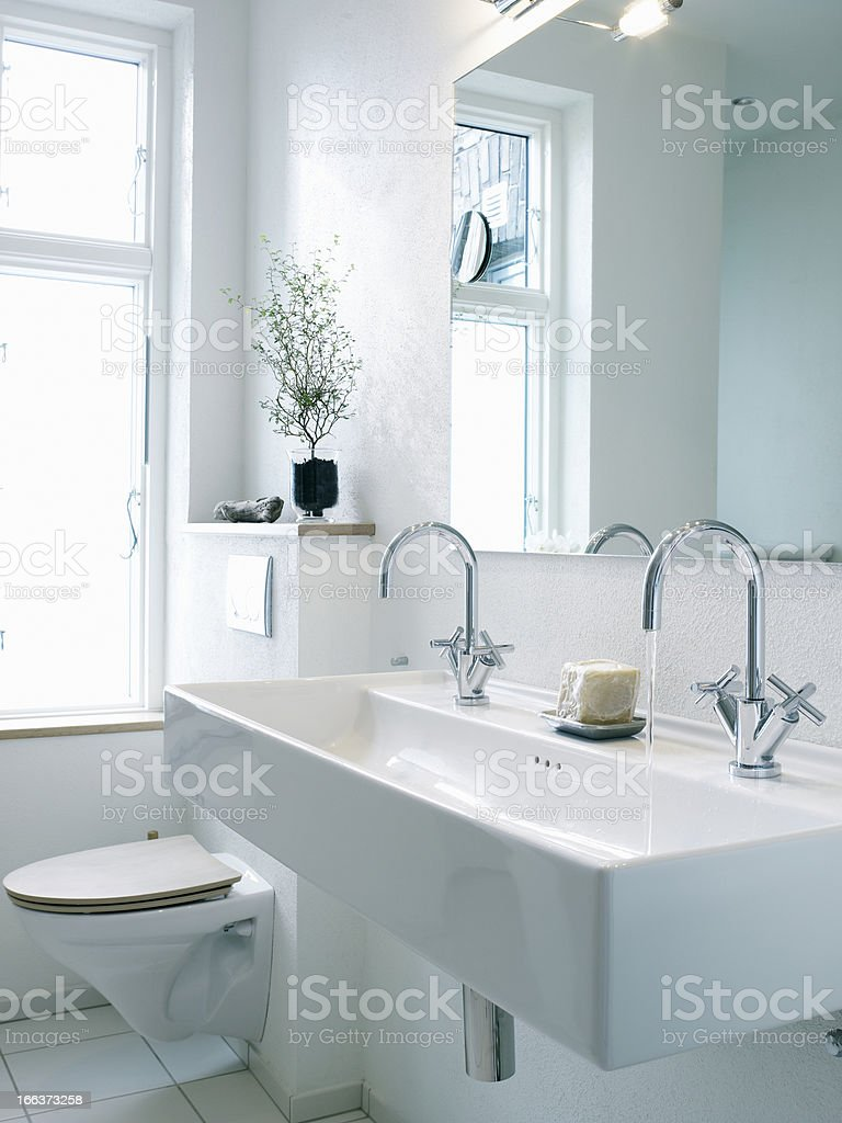 Washbasin with two faucets next to toilet stock photo
