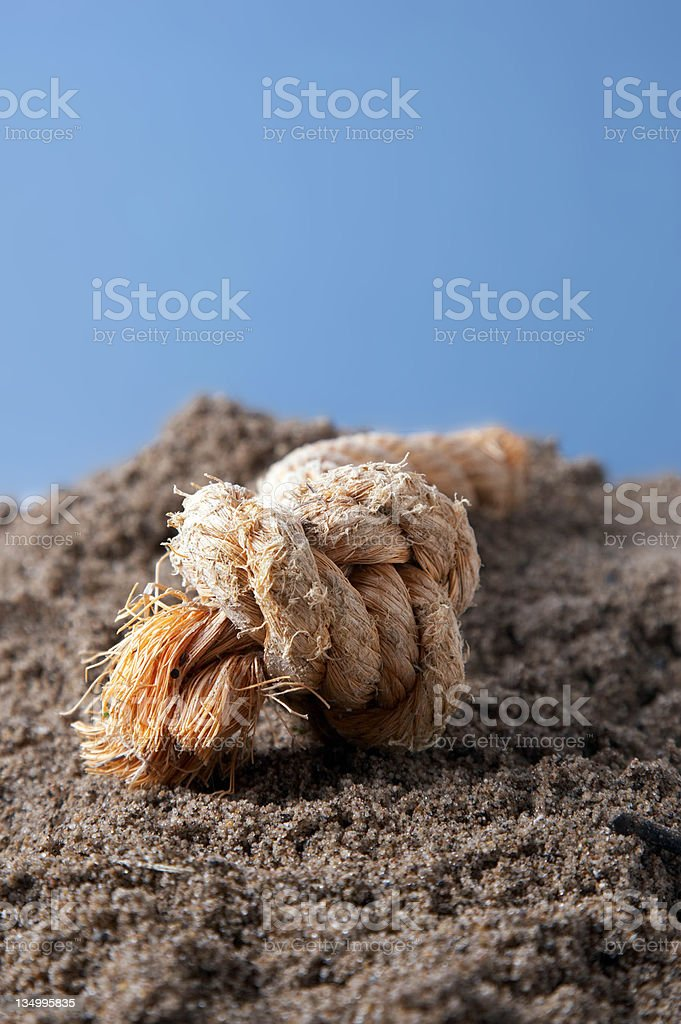 Washed up rope on sandy beach stock photo